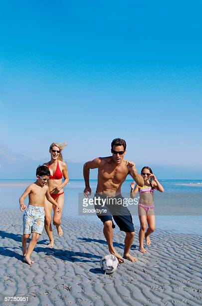 Parents and their children playing soccer on the beach