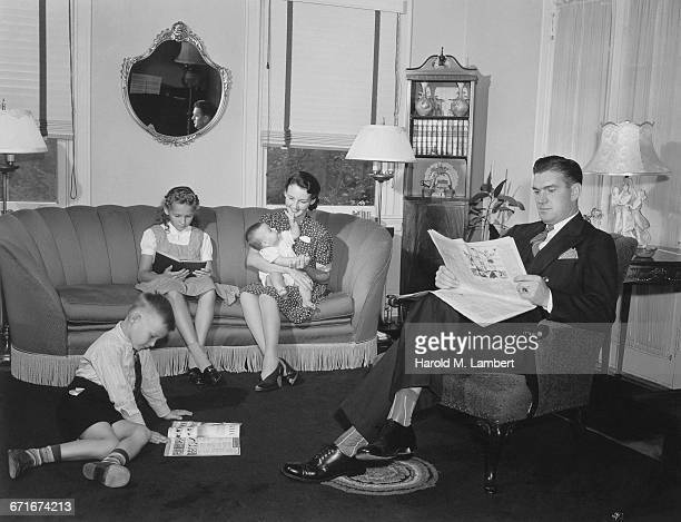 parents and their children sitting in living room - {{relatedsearchurl(carousel.phrase)}} ストックフォトと画像
