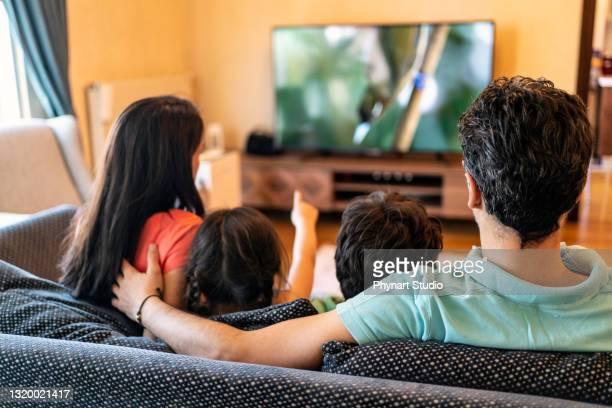 föräldrar och deras två barn tittar på tv tillsammans hemma - film and television screening bildbanksfoton och bilder