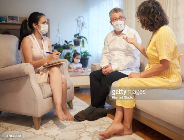 parents and therapist are sitting on the couch during a meeting about their child - persons with disabilities stock pictures, royalty-free photos & images