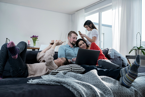 Parents and twin daughters on sofa using portable devices - gettyimageskorea