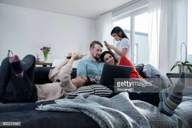 parents and twin daughters on sofa using portable devices - equipment stock pictures, royalty-free photos & images