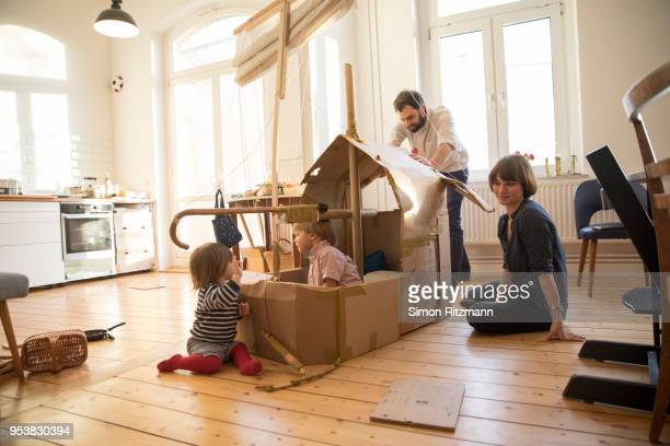 parents and two children playing with cardboard sailingboat at home - at home stock-fotos und bilder