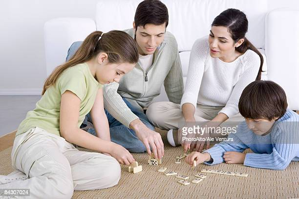Parents and two children seated on floor, playing dominoes together