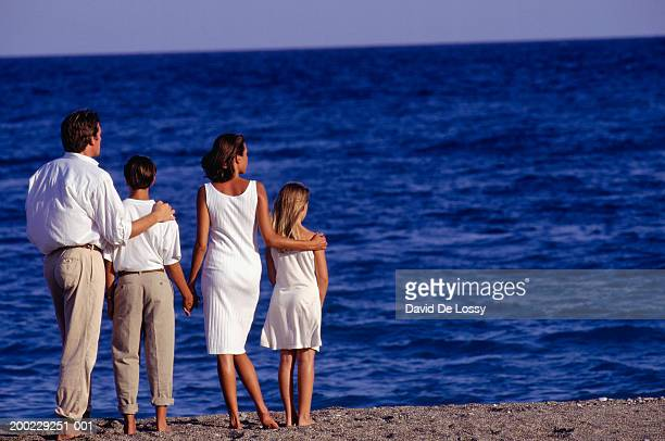 parents and two children (8-9) (10-11)  standing on beach by ocean, rear view - kin in de hand stock pictures, royalty-free photos & images