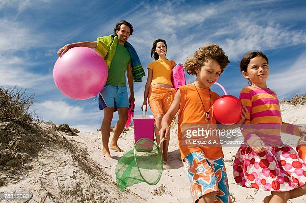 parents and two children walking on the beach, outdoors - girls with short skirts - fotografias e filmes do acervo