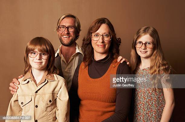 Parents and two children (9-11) wearing spectacles, smiling, portrait