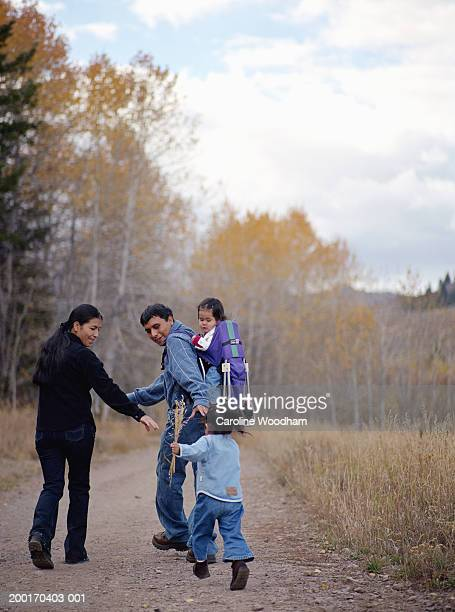 parents and two daughters (15 months-2 years) on footpath, rear view - 30 34 years stock-fotos und bilder