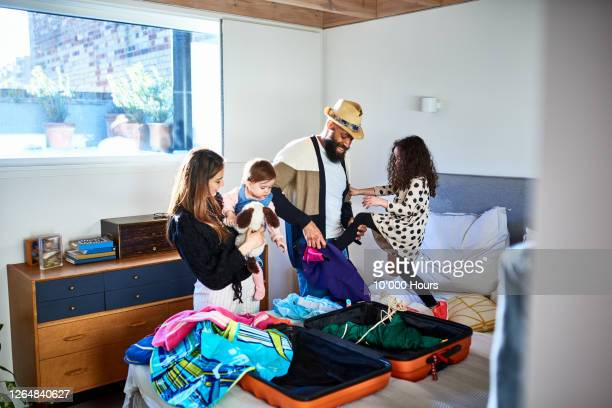 parents and two daughters packing suitcase for summer vacation - travel foto e immagini stock