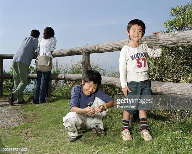 Parents and two sons (5-10) beside wooden fence (focus on boys)
