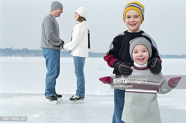 parents and two sons (2-5) ice skating on frozen lake (focus on boys) - frozen 2 stock pictures, royalty-free photos & images