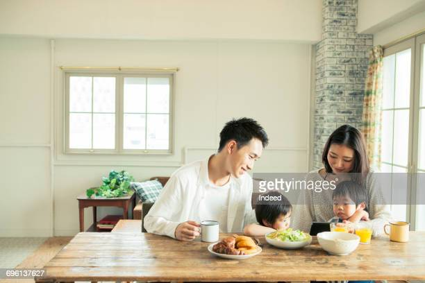 Parents and two sons looking at smart phone at table