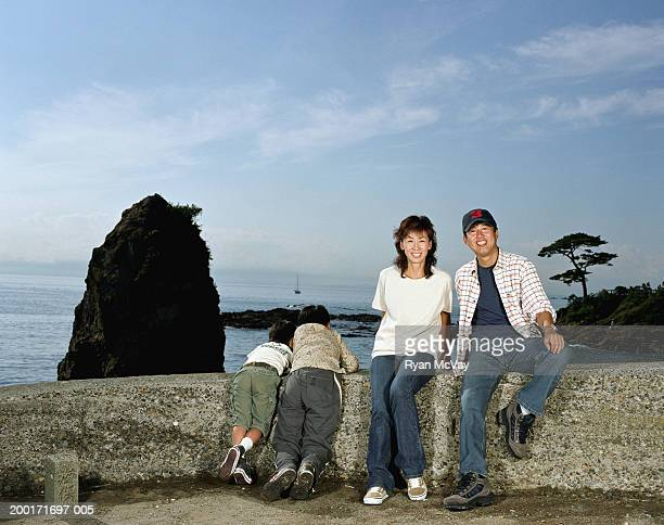 Parents and two sons (5-10) on rock wall beside sea, parents smiling