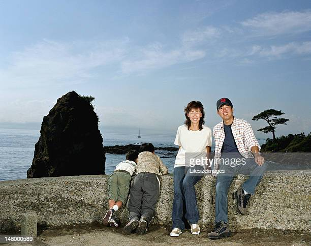 Parents and two sons (5-10) on rock wall beside sea