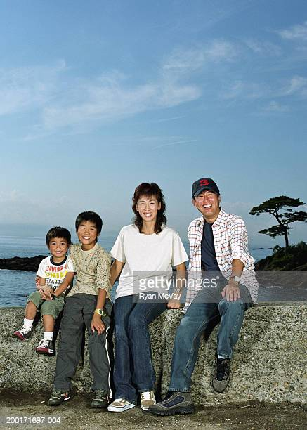 Parents and two sons (5-10) sitting on rock wall beside sea, portrait
