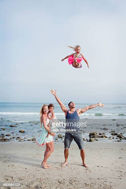 Parents and two young girls fooling around on beach