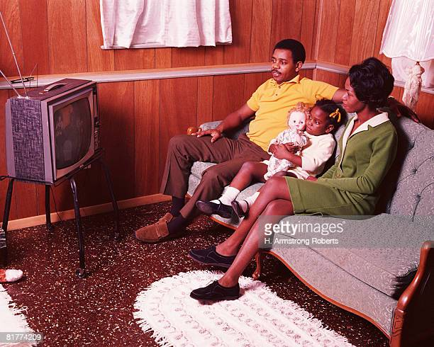 Parents and young daughter sitting in living room, watching television. (Photo by H. Armstrong Roberts/Retrofile/Getty Images)
