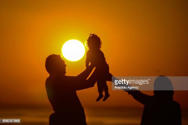 Parents are seen as they hold a baby during a sunset over Van Lake on August 21 2017 in Van Turkey