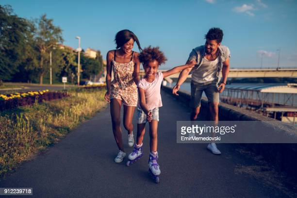 parents assisting their daughter while roller skating at sunset - roller skating stock pictures, royalty-free photos & images