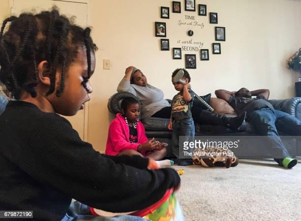 Parents Carolyn Harrison and Samson Harrison R catch a quick break as their children Malik Harrison L Madison Banks and Makhi Harrison entertain...