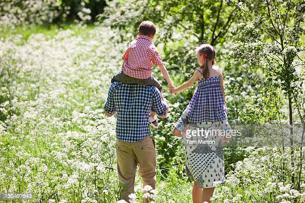 Parents carrying children on their shoulders outdoors