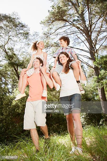 Parents carrying kids on shoulders in woods