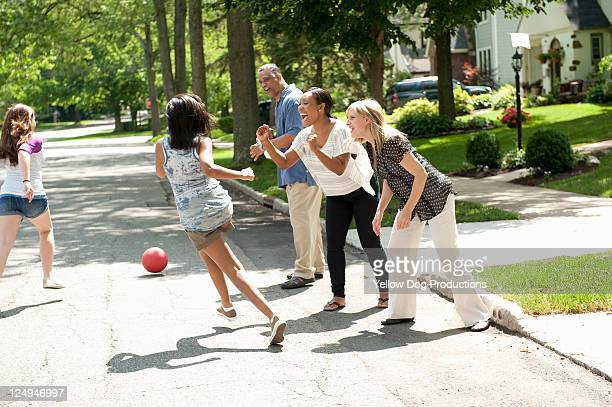 parents cheering neighborhood kids playing - kickball stock photos and pictures