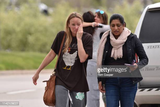 Parents comfort each other at the scene of a shooting in which at least seven students were injured at the STEM School Highlands Ranch on May 7 2019...