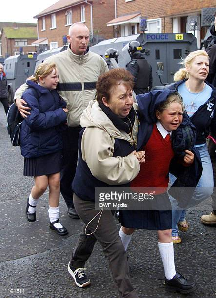 Parents comfort their daughters in the aftermath of a blast bomb attack on police September 5, 2001 in North Belfast. The bomb was thrown at police...