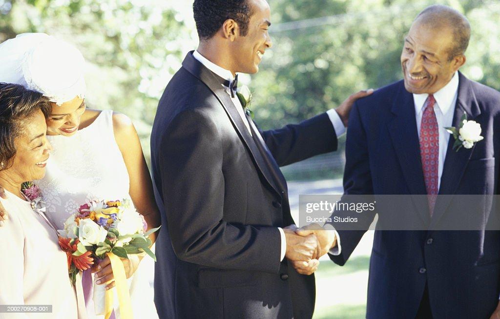 parents congratulating bride and groom in garden stock photo