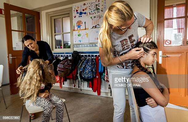 Parents control children's hair to see if they are infested by head lice at a primary school in Scheveningen on August 31 2016 / AFP / ANP / Remko de...