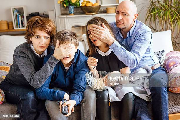 parents cover their children's eyes and watching tv - forbidden stock pictures, royalty-free photos & images