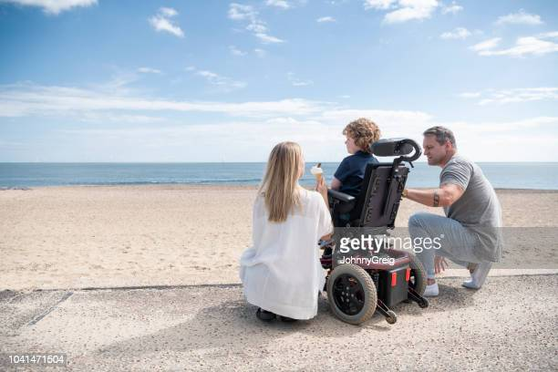 parents crouching by son in wheelchair at beach - acessibilidade imagens e fotografias de stock