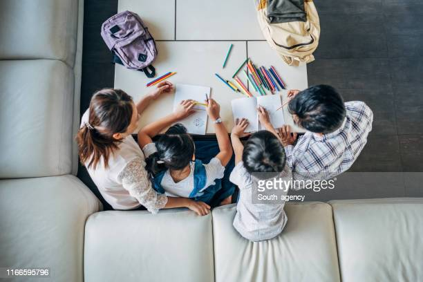 parents doing homework with daughter and son at home - home schooling stock pictures, royalty-free photos & images