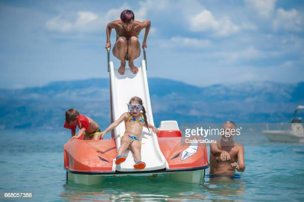 parents enjoying with children on pedalo boat - pedal boat stock pictures, royalty-free photos & images