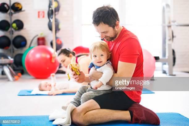 モダンなジムで赤ちゃんと運動の両親。