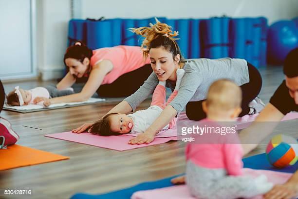 Parents avec leurs petits exercices dans une salle de sport