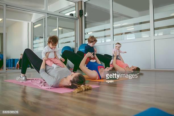 Parents avec leurs bébés de l'exercice dans la salle de Salle de gym