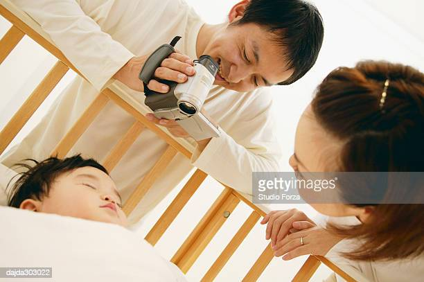 Parents filming their baby over the baby bed