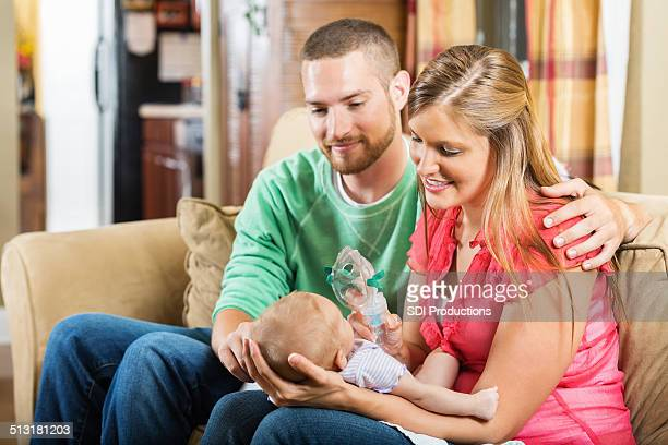 parents giving baby with cystic fibrosis a breathing treatment - cystic fibrosis stock photos and pictures