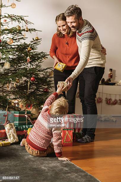 parents giving christmas gifts to little child - gift lounge stock-fotos und bilder