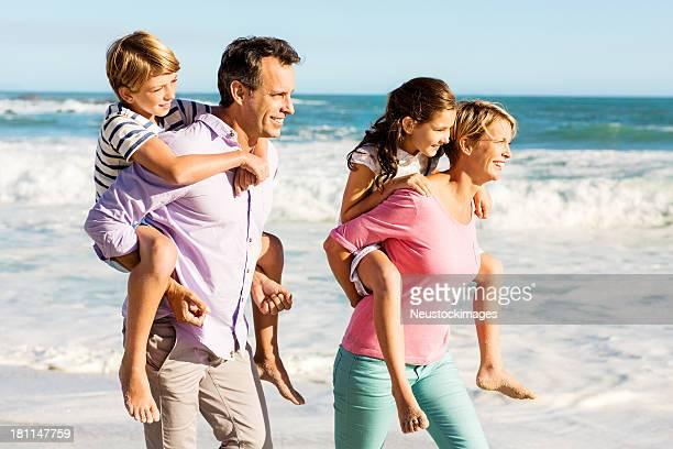 Parents Giving Piggyback Ride To Children On Beach