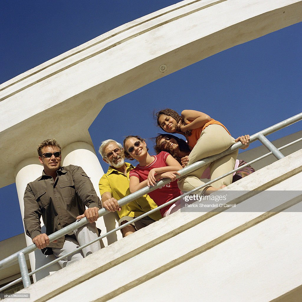 Parents, grandfather and children leaning on railing, low angle view : Stockfoto