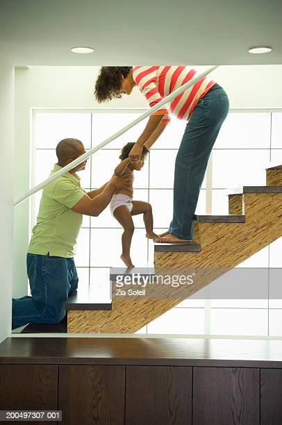 Parents helping daughter (2-3) ascend staircase at home, side view