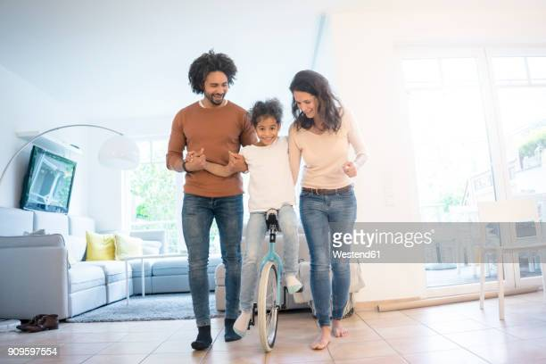parents helping daughter to ride a unicycle in the living room - couple mixte noir blanc photos et images de collection