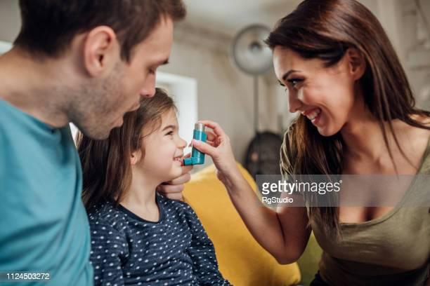 os pais ajudando filha usando bombinha de asma - asmático - fotografias e filmes do acervo