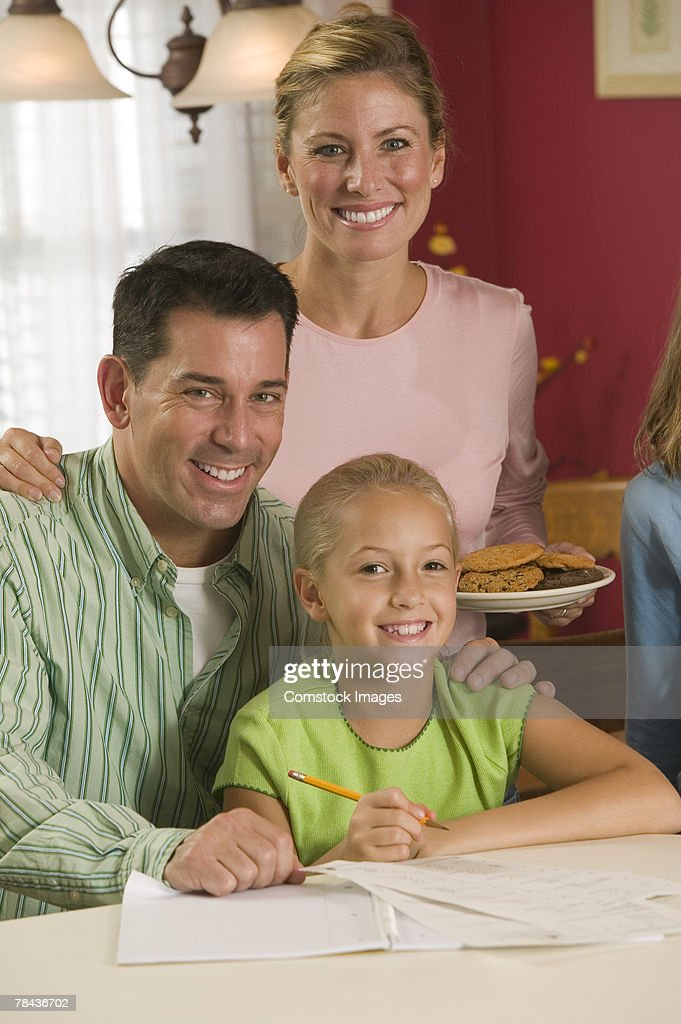 Parents helping daughter with homework : Stockfoto