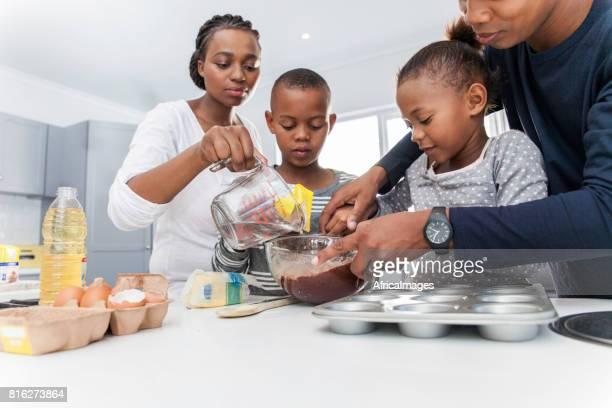 Parents helping their children bake muffins.