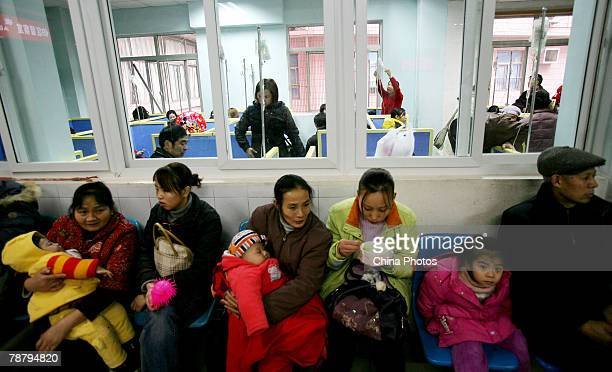 Parents hold their children who wait for treatment outside a IV room at a hospital on January 7 2008 in Chongqing Municipality China According to a...