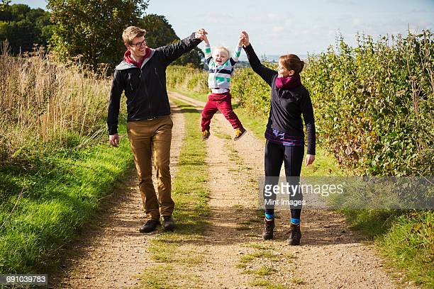 Parents holding a small boys hands and lifting him up in the air.